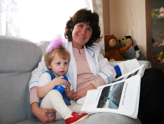 Luba and Mama Olga reading her soft book at the Partizansk Baby Hospital