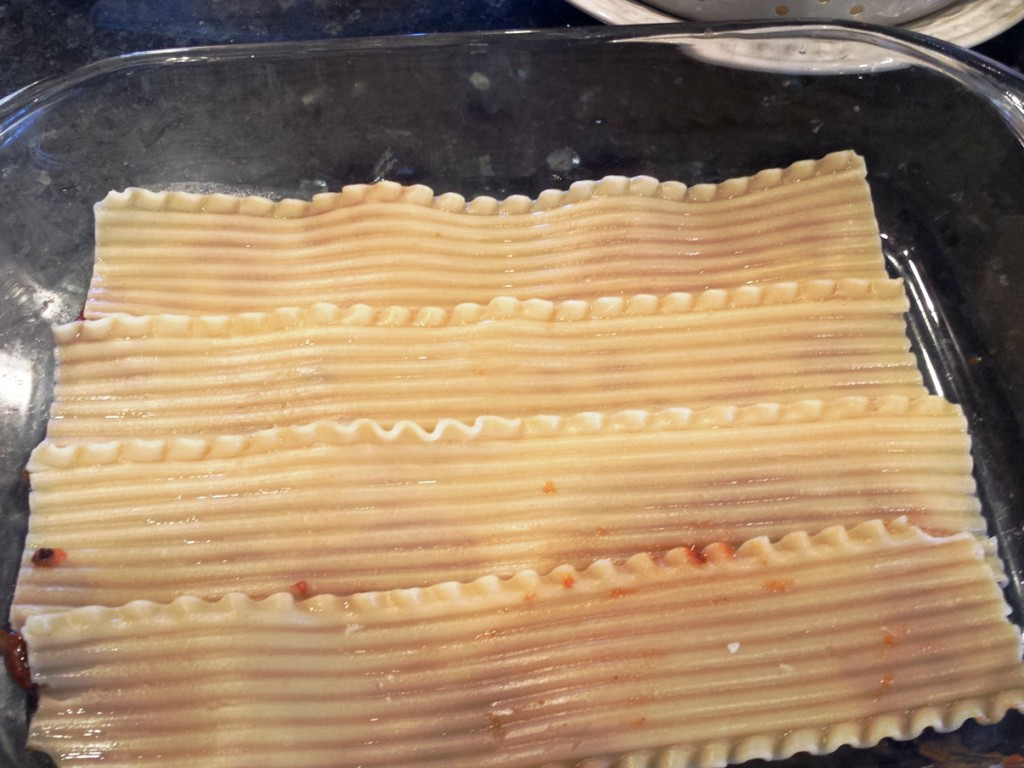 """Spread a small amount of Monster Spaghetti Sauce over bottom of 9""""x 13"""" baking pan.  Lay four lasagna noodles for base layer and spread 2 cups of sauce over noodles."""